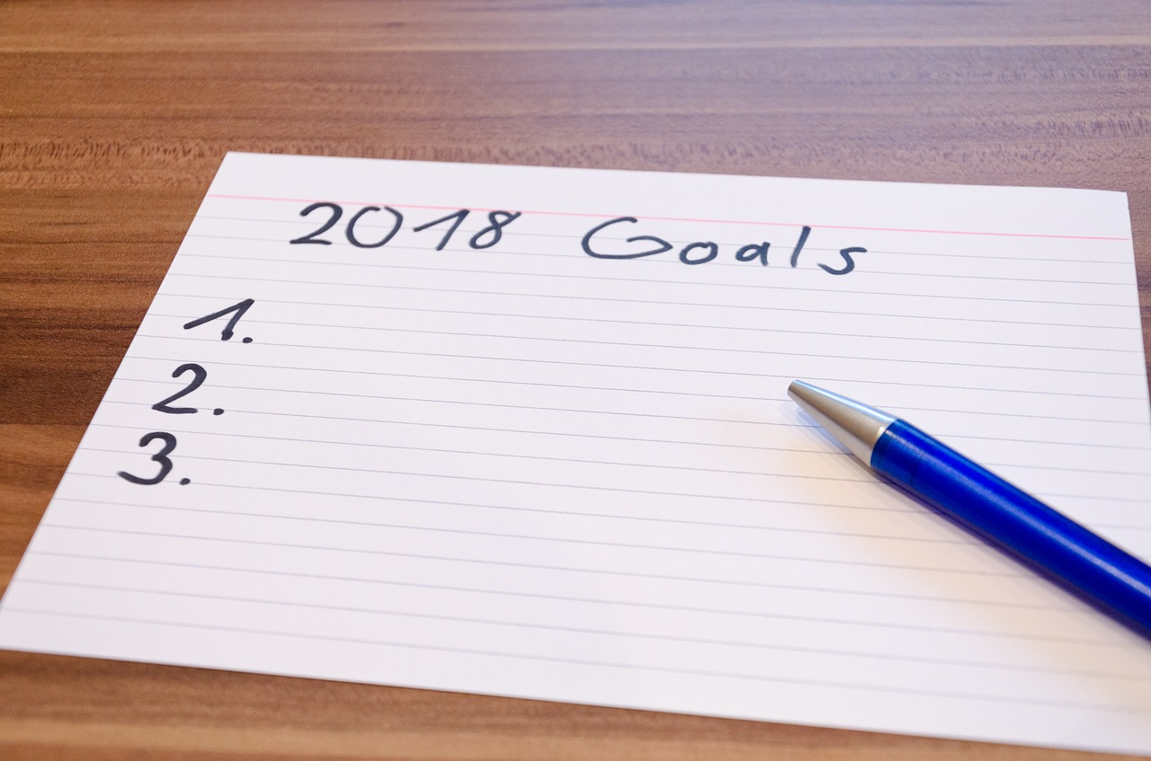 A piece of paper headed with 2018 goals, then numbered points and a pen, ready to write them down.